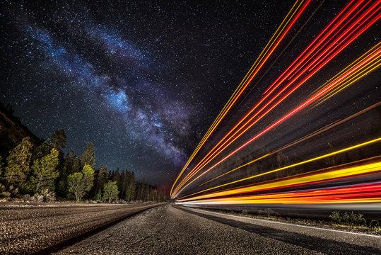 Light streaks on the highway under the Milky Way
