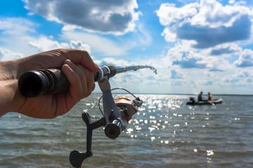Hands fisherman keep spinning rod