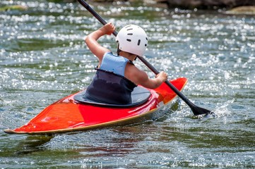 A teenager trains in the art of kayaking. Slalom boats on rough river rapids. The child is skillfully engaged in rafting.