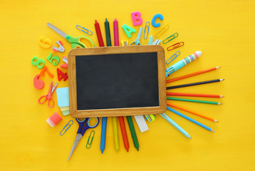 Back to school concept on yellow wooden background with empty blackboard