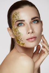 Woman Skin Care. Female With Gold Mask Touching Facial Skin