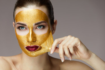 Beauty Product. Closeup Of Sexy Woman Removing Golden Mask