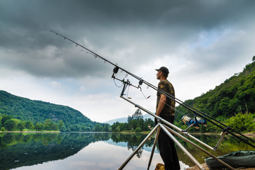 Fishing adventures, carp fishing. Angler on the shore of a lake in a morning with dark sky and grey clouds