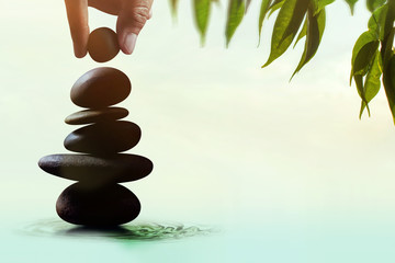 Balance concept between of Life and work present by Hand setting a natural zen rock stone stack, Surrounded with Leaf and Ripple, Side view