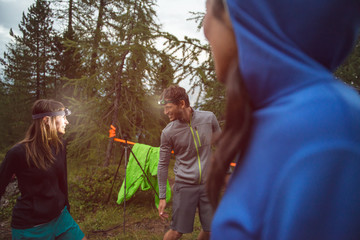 Man and woman joking and smiling with headlamp in evening near camping. Group of friends people summer adventure journey in mountain nature outdoors. Travel exploring Alps, Dolomites, Italy. Wall mural