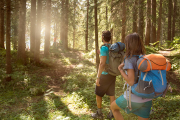 Man and woman with backpack walking on hiking trail path in forest woods during sunny day.Group of friends people summer adventure journey in mountain nature outdoors.Travel exploring Alps,Dolomites