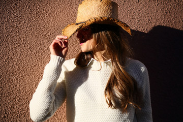 Stylish young woman holding cowboy hat, sunlight, on beige textured background, copy space