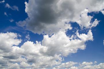 Heavy rain clouds flying in the deep blue summer sky