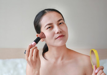 Portrait of attractive young adult woman applying blusher.