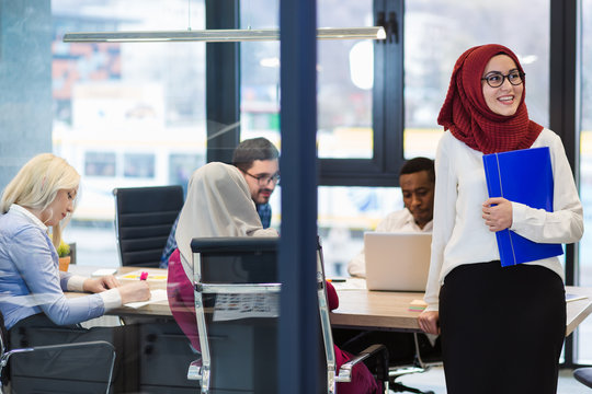 Arabian Businesswoman in office with Businesspeople meeting in the background, Arabian woman wearing Hijab in office with her colleagues in background