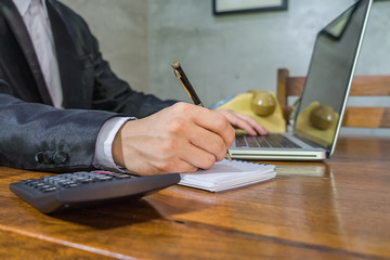 Businessman doing finances with using calculator and writing note in office