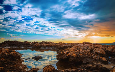 A seaside landscape at sunset with white boulders in foreground and dramatic clouds