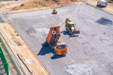 Dump truck unloads asphalt at the construction site of the school stadium