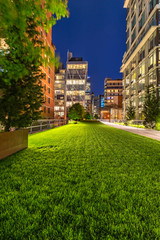 Highline promenade at twilight with illuminated high-rises in Chelsea. Manhattan, New York City
