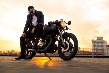 Handsome rider man with beard and mustache in black leather biker jacket and denim sit on classic style cafe racer motorcycle. Bike custom made in vintage garage. Brutal fun urban lifestyle.