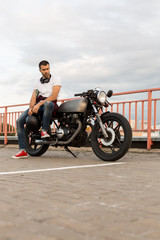 Handsome rider guy with beard and mustache in red sneakers and black moto glasses sit on classic style biker cafe racer motorcycle. Bike custom made in vintage garage. Brutal fun urban lifestyle.