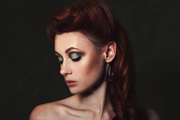 Beauty portrait of a beautiful redhead girl with bright make-up