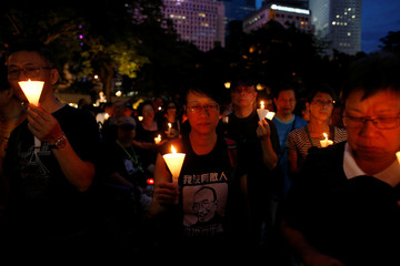 Protesters carrying candles take part in a march to mourn the death of Nobel laureate Liu Xiaobo, in Hong Kong
