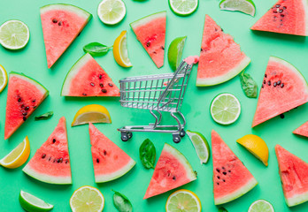 cutted lemons and limes with watermelon near shopping cart