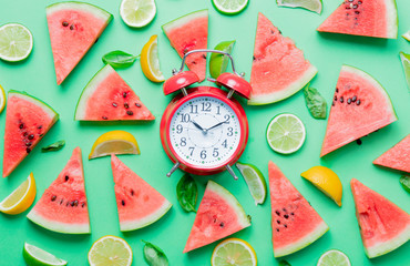 cutted lemons and limes with watermelon with alarm clock