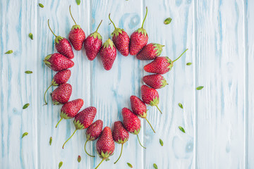 Fresh strawberries array heart shape on old wooden background