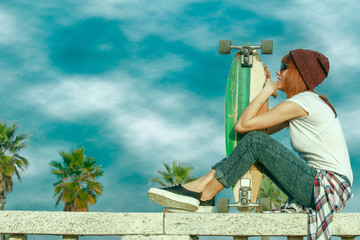 skater girl in jeans sitting and holding skateboard on a sunny day with cloudy sky. deep blue sky and saturated colors