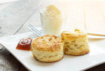 Scones with cream and jam in white plate on wooden desk