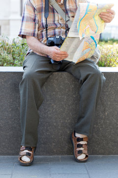 Old pensioner in socks and sandals searching destination on map