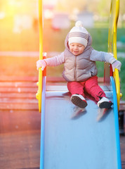 One year old baby boy toddler at playground slide