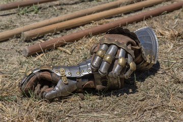 Detail of gloves as part of a metallic armor, on a reenactment with costumed characters and medieval armor with chainmail, helmet swords and shields. Medieval demonstration and recreation