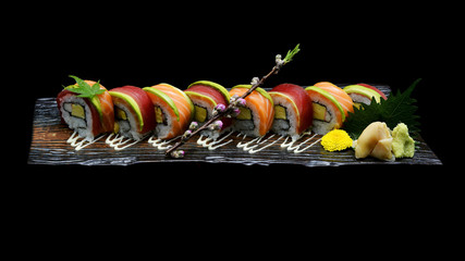 Tuna sushi maki roll and Salmon sushi maki roll. Japanese sushi fish roll on black isolated background. Japanese tradition fusion food style.