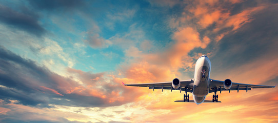 Poster Airplane Landing airplane. Landscape with white passenger airplane is flying in the blue sky with multicolored clouds at sunset. Travel background. Passenger airliner. Business trip. Commercial aircraft