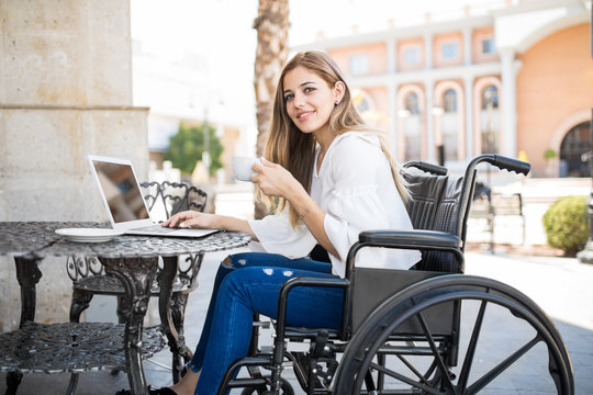 Pretty woman in wheelchair at a cafe