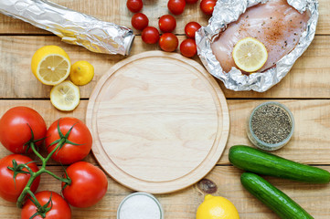 Background with round wooden board and variety of products. Raw chicken breast, lemon, tomatoes, cucumber and seasoning