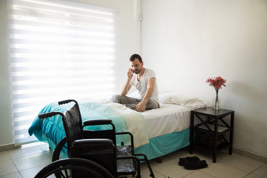Disabled man making a call from bed