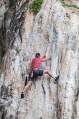 Tourist man climbing on a limestone wall on Krabi province at Thailand.