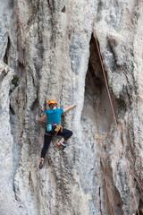Tourist woman climbing on a limestone wall on Krabi province at Thailand.