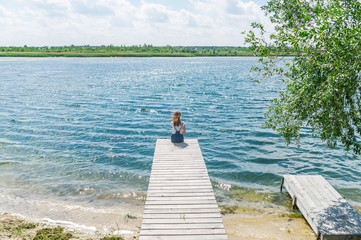 Young beautiful girl sitting on jetty river on background