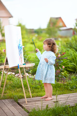 cure toddler girl paints on the easel in the garden
