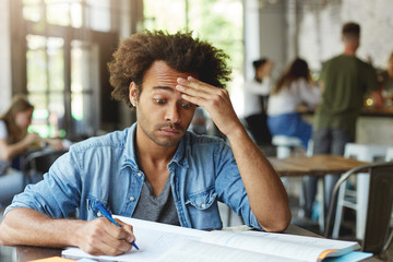 Frustrated confused young college student with Afro hairstyle rubbing forehead, trying hard to understand complicated mathemtical problem while doing homework at cafe, using pen for making notes