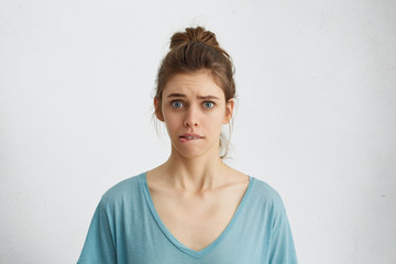Young female having worried look biting her lower lip nervously looking with her blue anxious eyes in camera isolated over white background. Cute woman in casual clothes with nervous expression