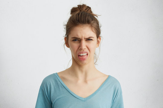 Grumpy woman showing her disgust while frowning face with dissastisfaction showing her tongue. Young blue-eyed female not wanting to do something having discontent look expressing her non-compliance