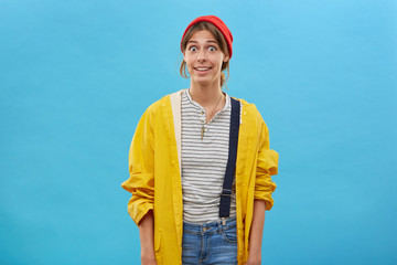 Surprised woman wearing casual clothes posing against blue background looking with bugged eyes wondering. Young female in loose yellow raincoat and red hat with excited look isolated over studio wall