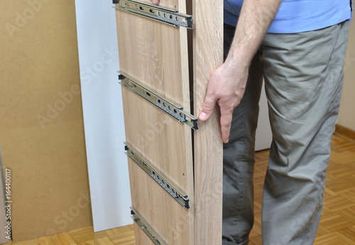 Man Assembling Parts Of A New Piece Of Furniture With Drawer Slides