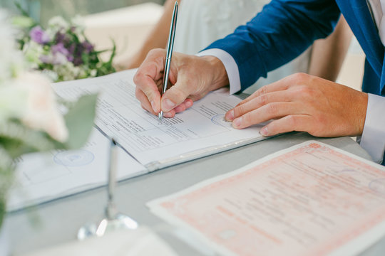 The groom signs the marriage registration documents. Young couple signing wedding documents. Man signs the documents