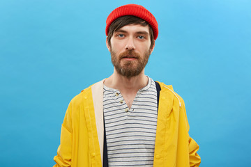 Bearded sailor dressed in red hat and yellow anorak posing against blue background. Serious man with beard having blue charming eyes dressed casually posing at studio. Fisherman going to angling