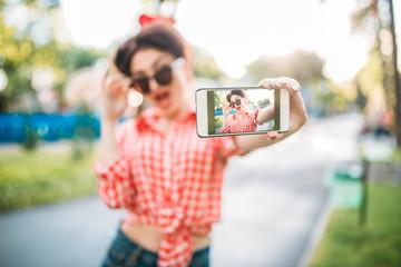 Pin up girl in sunglasses, selfie shot in park