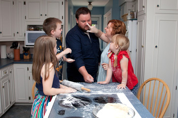 A family of five baking together before a food fight breaks out.
