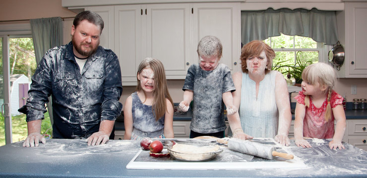 an angry family in the kitchen after a food fight and baking an apple pie.