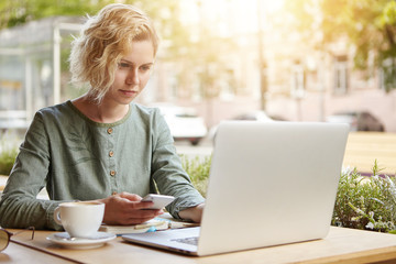 Beautiful female with trendy hairstyle wearing elegant blouse sitting at outdoor cafe drinking coffee surounded with modern gadgets. Young blonde lady holding cell phone in hand searching information